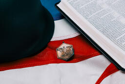 Military Helmet and Open Bible on an American Flag with a Military Medallion  image 3