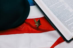 Military Helmet and Open Bible on an American Flag with a Military Medallion  image 2