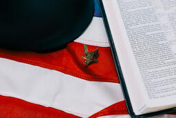 Military Helmet and Open Bible on an American Flag with a Military Medallion  image 1