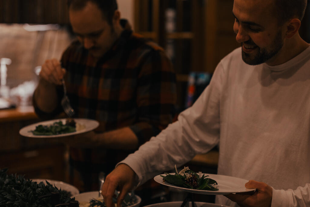Man Serving Up Salad at a Potluck large preview