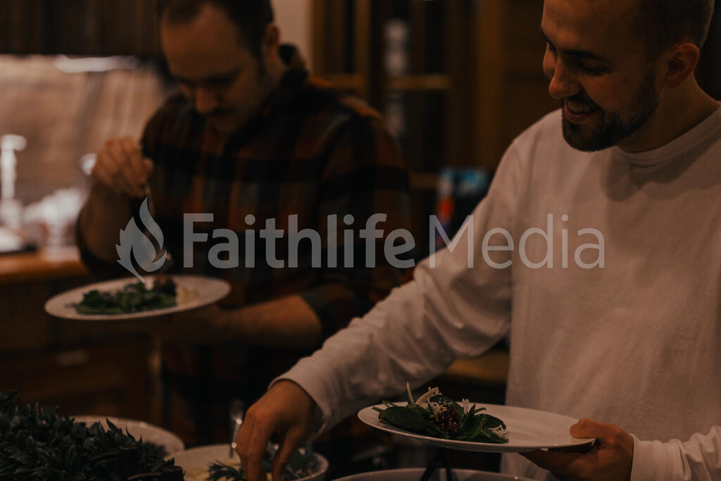 Man Serving Up Salad at a Potluck large preview