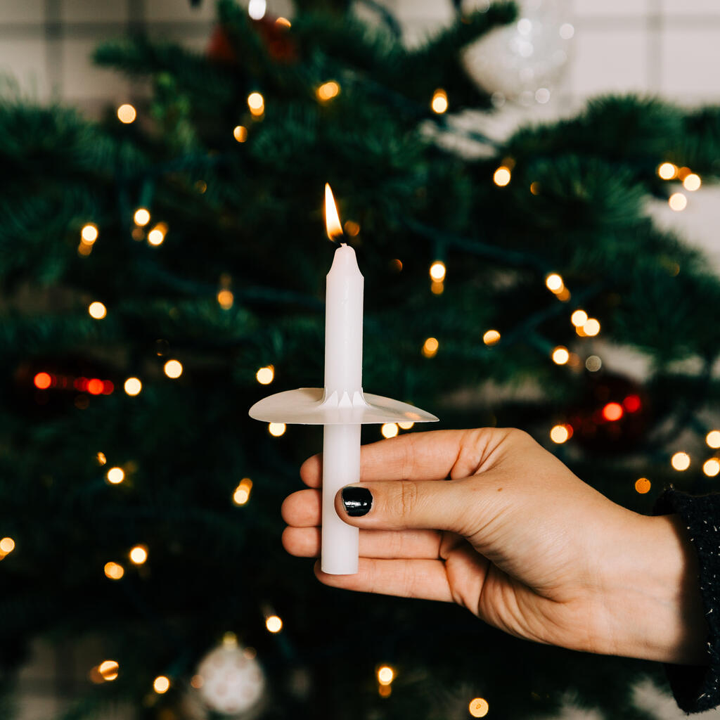 Hand in Frame Holding a Candle in Front of the Christmas Tree large preview