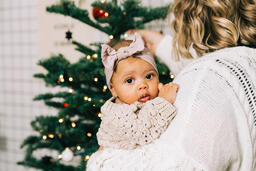 Woman Holding Her Baby and Decorating for Christmas  image 2
