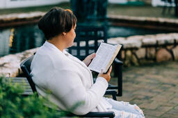 Woman Reading the Bible on the Patio Outside  image 3