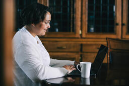 Woman Working on a Laptop with a Cup of Coffee at the Table  image 1