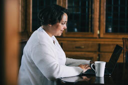 Woman Working on a Laptop with a Cup of Coffee at the Table  image 4