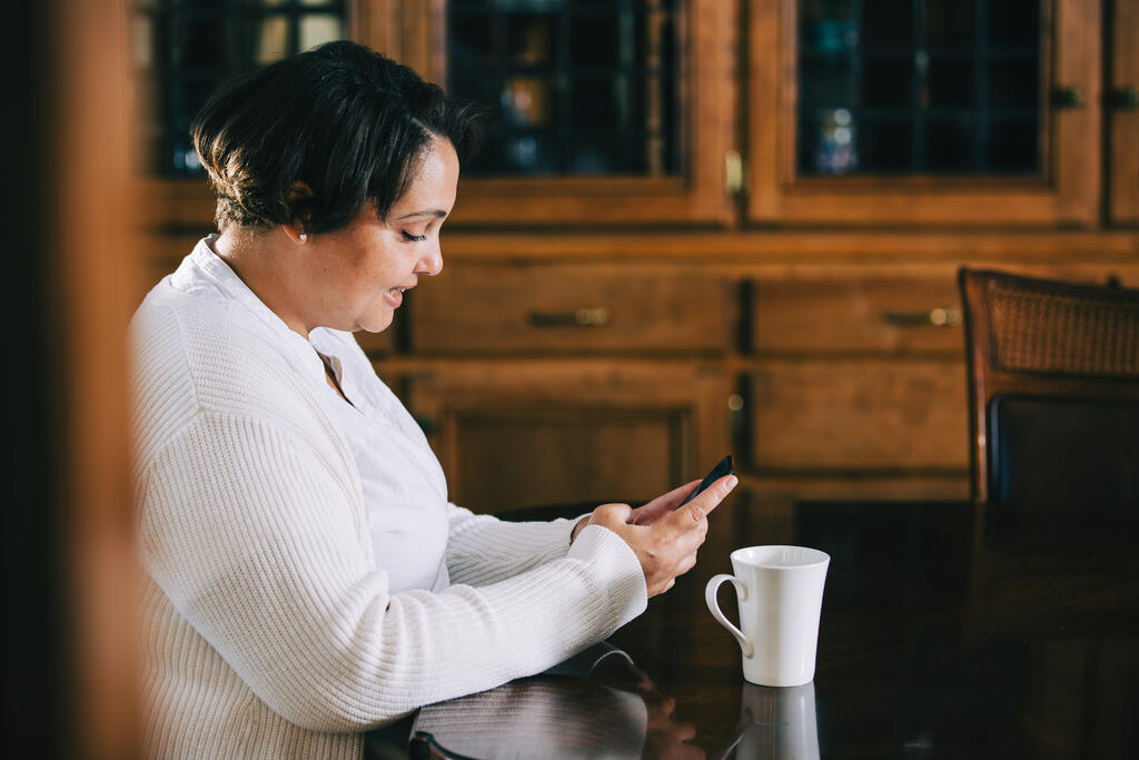 Woman Looking at Her Phone with a Cup of Coffee at the Table large preview