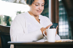 Woman Looking at Her Phone with an Open Bible and a Cup of Coffee  image 2