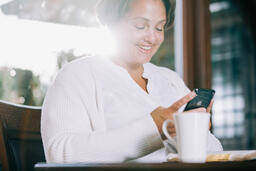 Woman Looking at Her Phone with an Open Bible and a Cup of Coffee  image 1