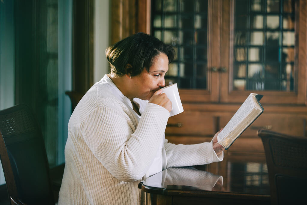Woman Reading the Bible and Drinking Coffee at a Table large preview