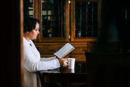 Woman Reading the Bible and Drinking Coffee at a Table  image 2