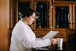 Woman Reading the Bible and Drinking Coffee at a Table  image 3