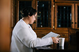 Woman Reading the Bible and Drinking Coffee at a Table  image 1