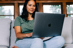 Woman Working on a Laptop and Smiling  image 2