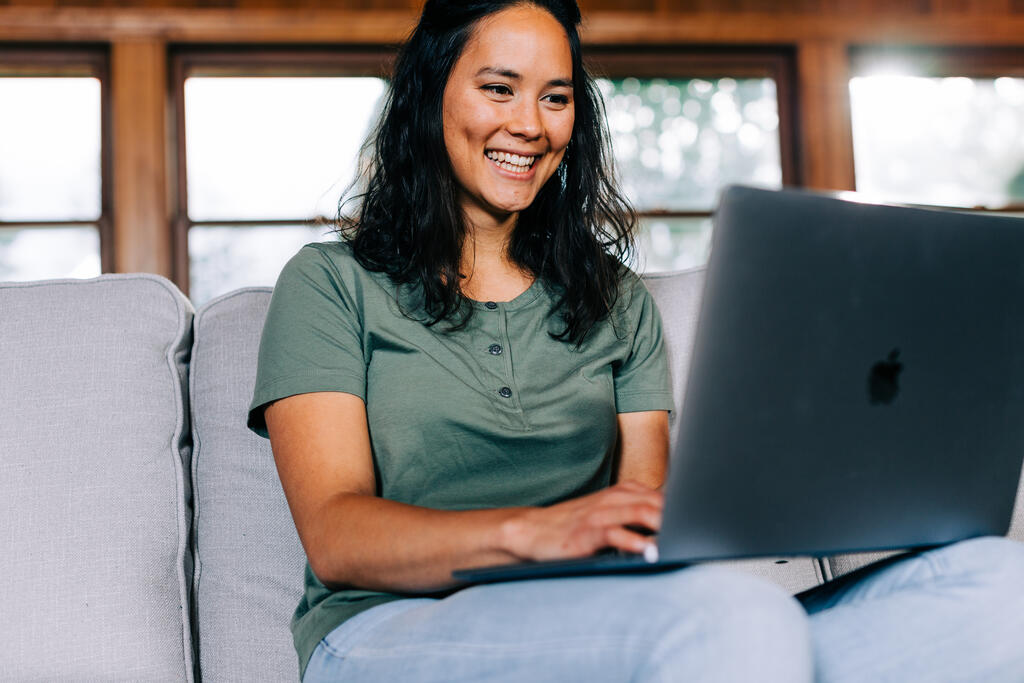 Woman Working on a Laptop and Smiling large preview