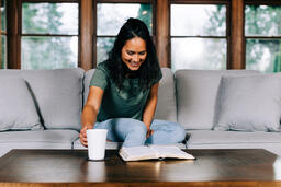 Woman Grabbing Her Cup of Coffee During Devotions  image 1