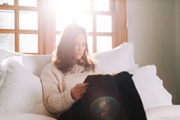 Woman Reading the Bible in Bed at Sunrise  image 1
