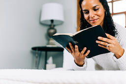 Woman Reading the Bible in Bed at Sunrise  image 2