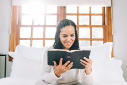 Woman Reading the Bible in Bed at Sunrise  image 3
