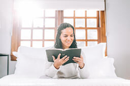 Woman Reading the Bible in Bed at Sunrise  image 4