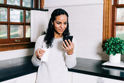 Woman Looking at Her Phone with a Cup of Coffee in the Kitchen  image 1