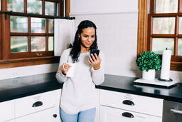 Woman Looking at Her Phone with a Cup of Coffee in the Kitchen  image 2