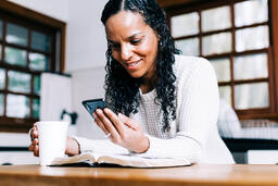 Woman Looking at Her Phone with an Open Bible and Cup of Coffee  image 2