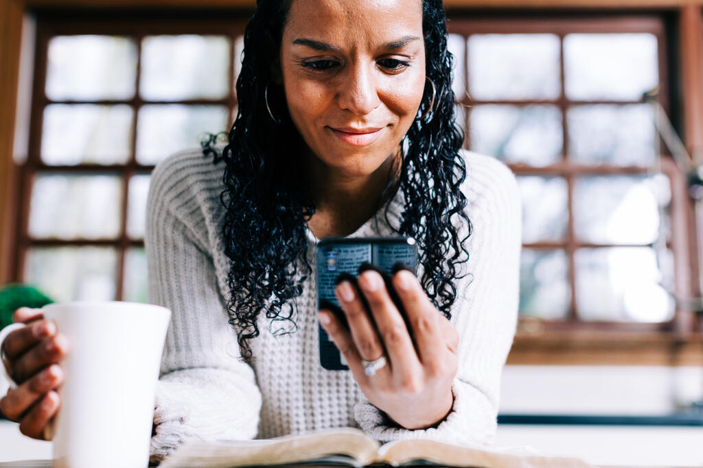 Woman Looking at Her Phone with an Open Bible and Cup of Coffee large preview