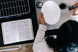 Woman Doing Dishes with the Bible Open Next to Her on the Counter  image 3