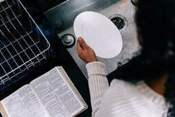 Woman Doing Dishes with the Bible Open Next to Her on the Counter  image 2