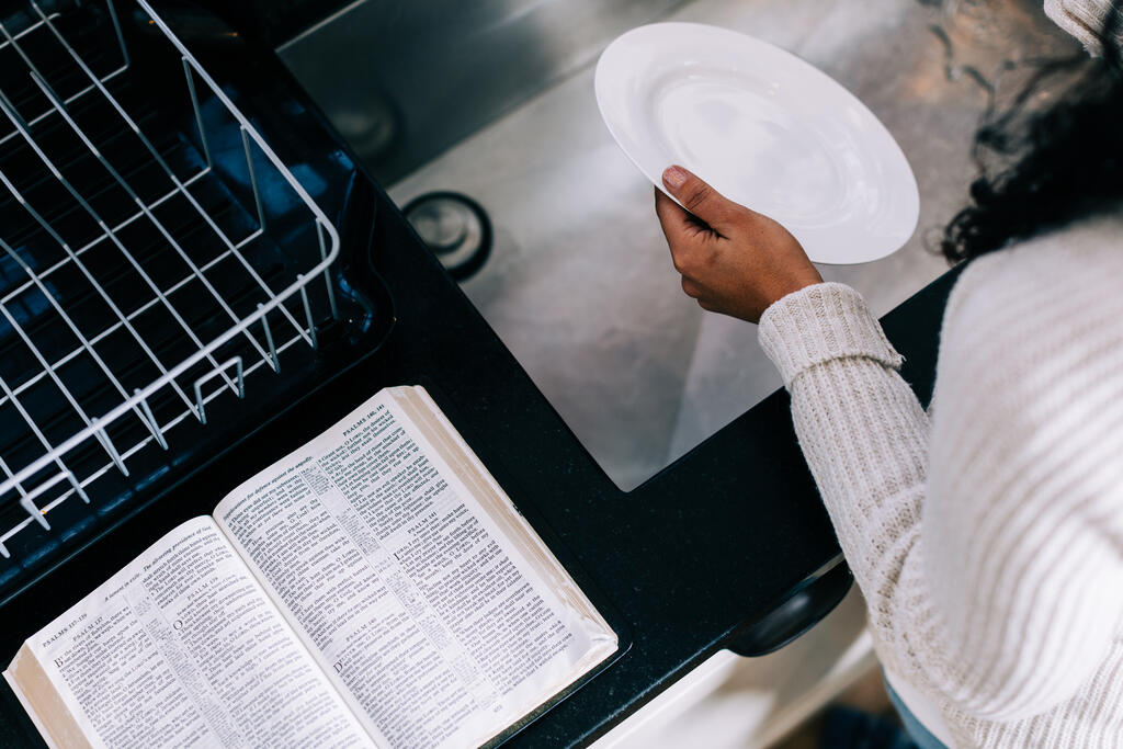 Woman Doing Dishes with the Bible Open Next to Her on the Counter large preview