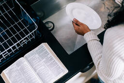 Woman Doing Dishes with the Bible Open Next to Her on the Counter  image 1