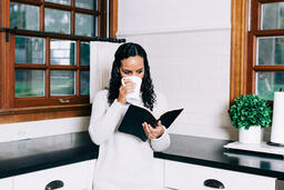 Woman Reading the Bible and Drinking Coffee in the Kitchen  image 2