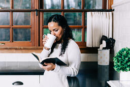 Woman Reading the Bible and Drinking Coffee in the Kitchen  image 1