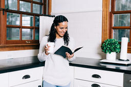 Woman Reading the Bible and Drinking Coffee in the Kitchen  image 4