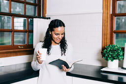 Woman Reading the Bible and Drinking Coffee in the Kitchen  image 3