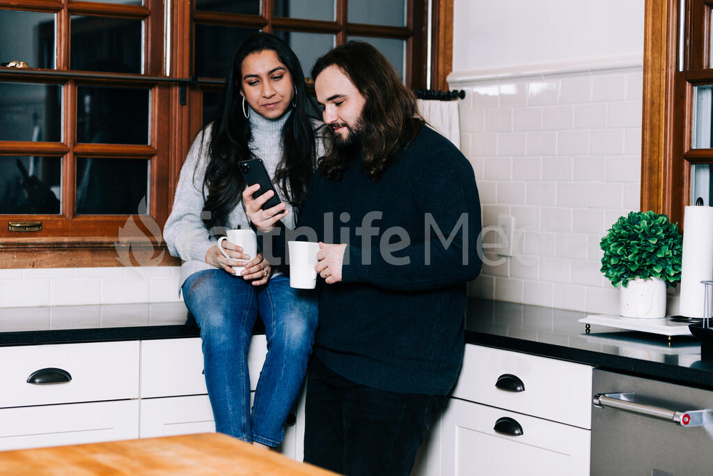Husband and Wife Looking at a Phone with Cups of Coffee in the Kitchen large preview