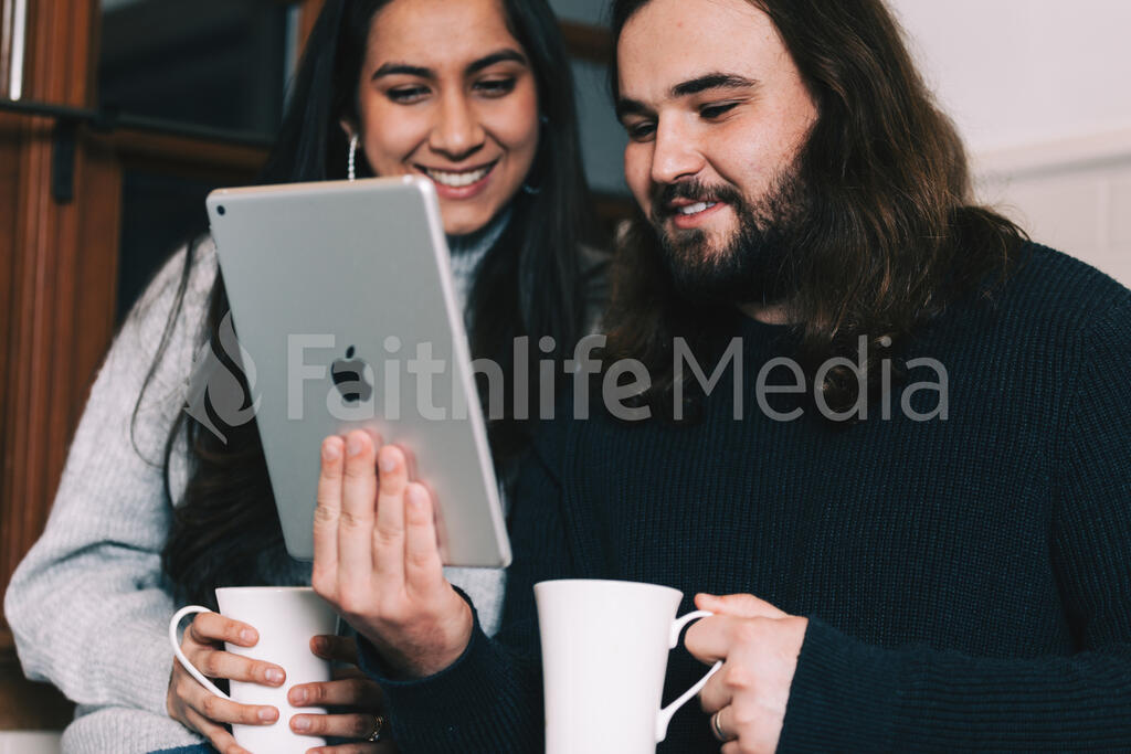 Husband and Wife Reading on a Tablet with Cups of Coffee large preview