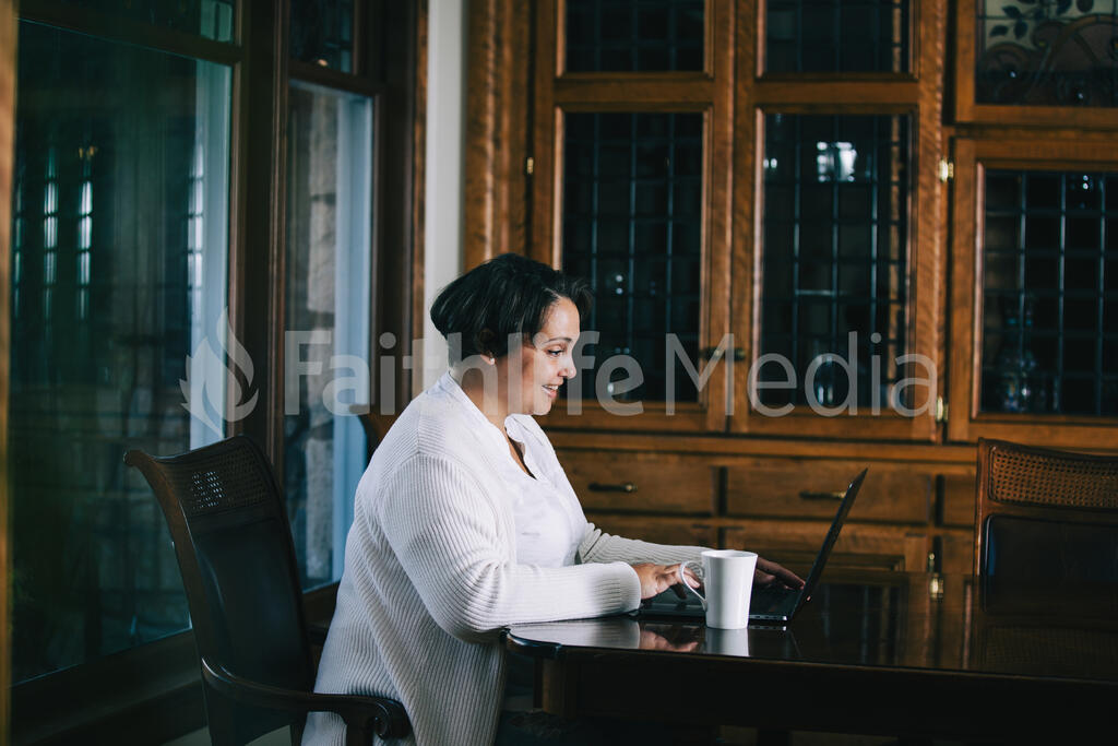 Woman Working on a Laptop with a Cup of Coffee at the Table large preview