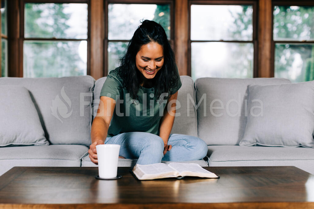 Woman Grabbing Her Cup of Coffee During Devotions large preview