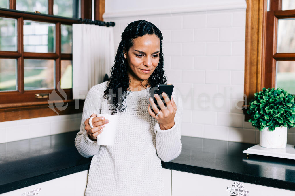Woman Looking at Her Phone with a Cup of Coffee in the Kitchen large preview