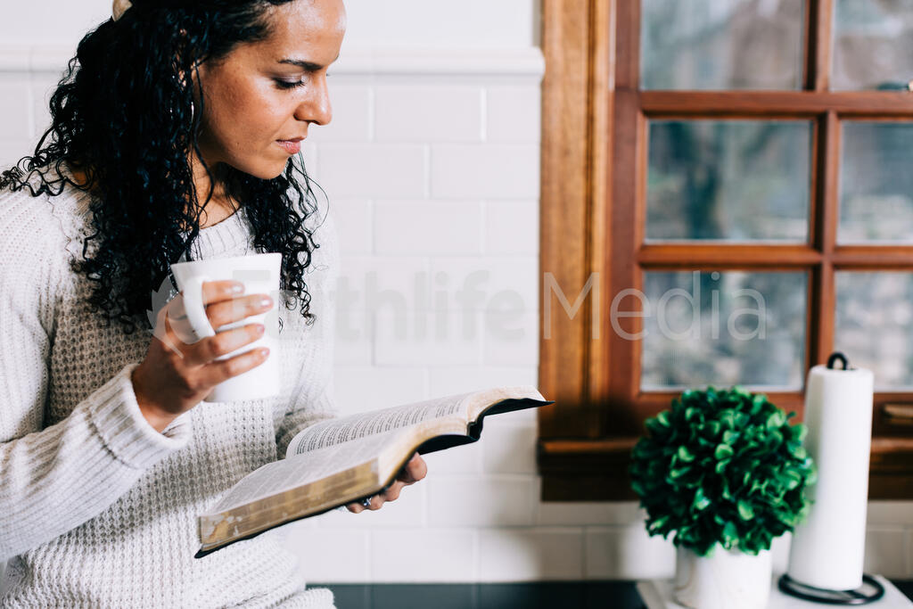 Woman Reading the Bible and Drinking Coffee in the Kitchen large preview
