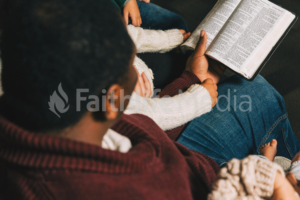 Family Reading the Bible Together at Christmastime large preview