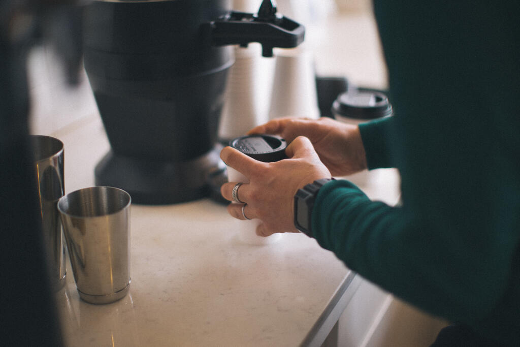 Barista Putting a Lid on a Cup of Coffee large preview