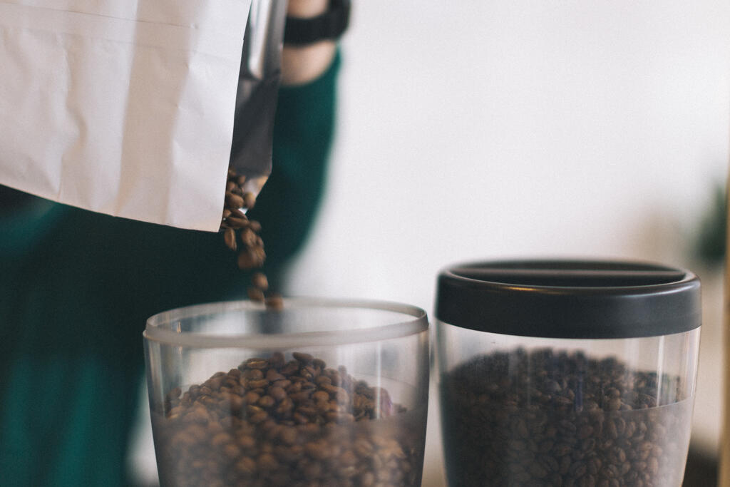 Barista Pouring Coffee Beans into a Grinder large preview