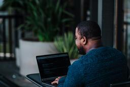 Man Facing Away Working on Laptop  image 4