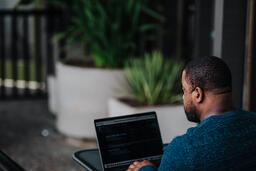 Man Facing Away Working on Laptop  image 6