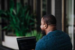 Man Facing Away Working on Laptop  image 3