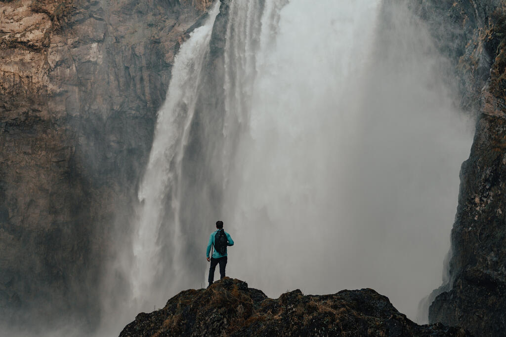 Hiker Standing in Front of a Waterfall large preview
